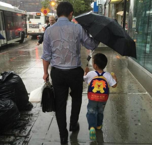 Bố cầm ô che chở con dưới trời mưa